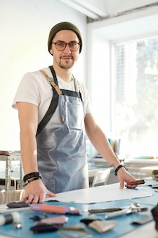 テーブルで作業しながらあなたを見ているエプロンで若い成功したプロの革細工人