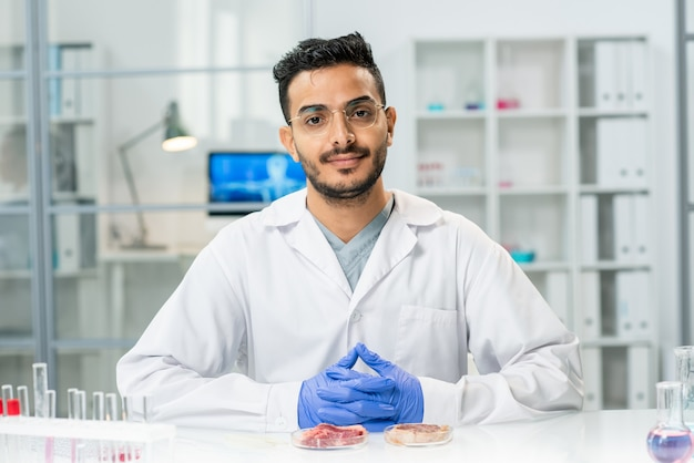 Young successful scientific researcher in whitecoat looking at you while sitting by workplace with samples of raw vegetable meat in petri dishes