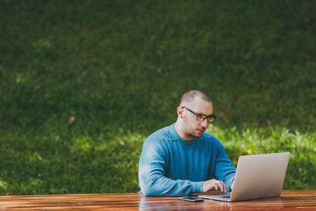 屋外で作業ラップトップを使用して都市公園で携帯電話とテーブルに座っているカジュアルな青いシャツのメガネで若い成功した真面目なスマートマンのビジネスマンまたは学生。モバイルオフィスのコンセプト。スペースをコピーします。