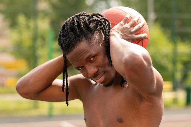 立っている間首の後ろにボールを保持している若い成功した上半身裸のバスケットボール選手