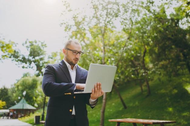 흰 셔츠, 고전적인 양복, 안경을 쓴 젊은 성공적인 똑똑한 사업가. 자연 배경에서 야외 도시 공원에 서서 랩톱 pc 컴퓨터에서 일하는 남자. 모바일 오피스, 비즈니스 개념입니다.