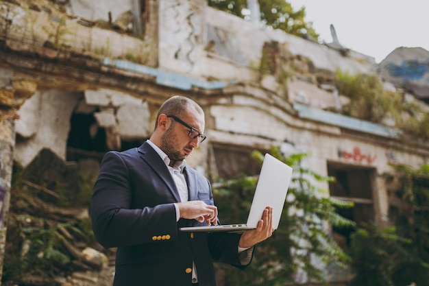 白いシャツ、クラシックなスーツ、メガネで若い成功したスマートビジネスマン。廃墟、破片、屋外の石造りの建物の近くに立ってラップトップpcコンピューターで作業している男性。モバイルオフィス、ビジネスコンセプト。