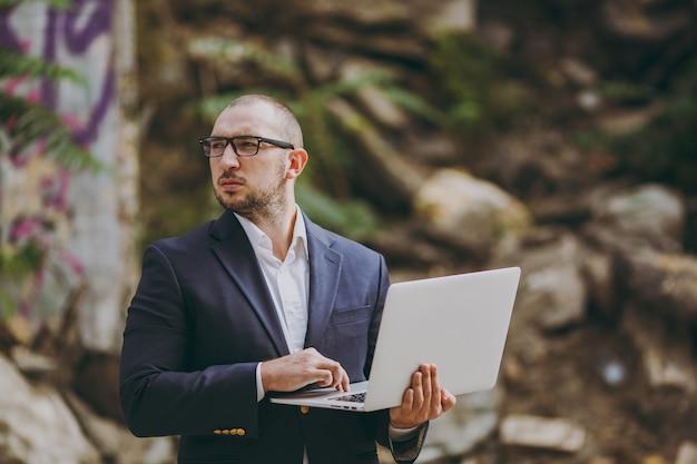 흰 셔츠, 고전적인 양복, 안경을 쓴 젊은 성공적인 똑똑한 사업가. 남자는 야외에서 폐허, 파편, 석조 건물 근처에 서서 랩톱 pc 컴퓨터에서 작업합니다. 모바일 오피스, 비즈니스 개념입니다.