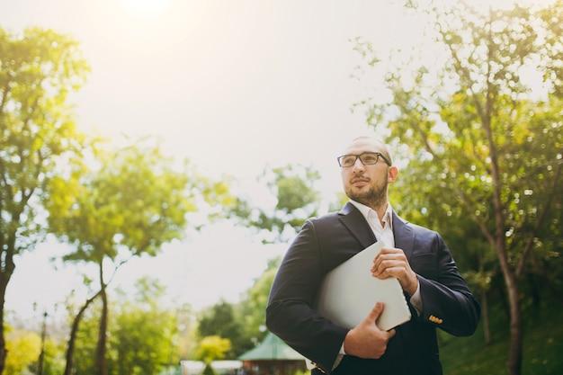 흰 셔츠, 고전적인 양복, 안경을 쓴 젊은 성공적인 똑똑한 사업가. 자연 배경 야외 도시 공원에서 노트북 pc 컴퓨터 휴대 전화와 함께 서 있는 남자. 모바일 오피스, 비즈니스 개념입니다.