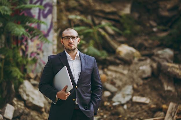 흰 셔츠, 고전적인 양복, 안경을 쓴 젊은 성공적인 똑똑한 사업가. 폐허, 파편, 야외 석조 건물 근처에 노트북 pc 컴퓨터 전화를 들고 서 있는 남자. 모바일 오피스, 비즈니스, 작업 개념입니다.