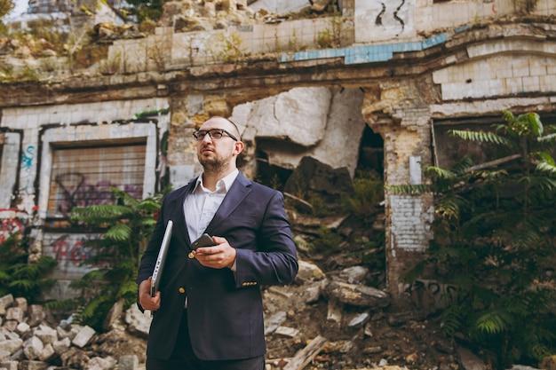 白いシャツ、クラシックなスーツ、メガネで若い成功したスマートビジネスマン。廃墟、破片、屋外の石造りの建物の近くにラップトップpcコンピューター電話で立っている男。モバイルオフィス、ビジネス、仕事のコンセプト。