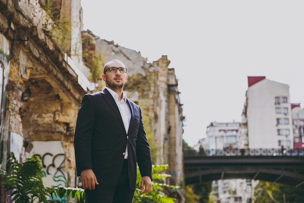 Young successful smart businessman in white shirt, classic suit, glasses. man standing near ruins, debris, stone building outdoors. mobile office, business concept. copy space for advertisement.
