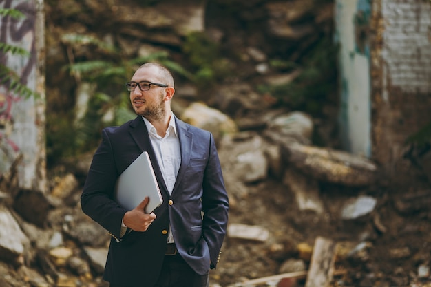 Young successful smart businessman in white shirt, classic suit, glasses. man standing with laptop pc computer phone near ruins, debris, stone building outdoors. mobile office, business, work concept. Free Photo