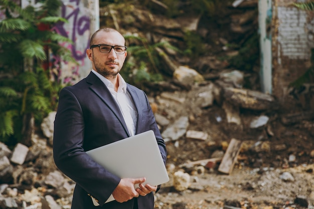 Young successful smart businessman in white shirt, classic suit, glasses. man standing with laptop pc computer phone near ruins, debris, stone building outdoors. mobile office, business, work concept.