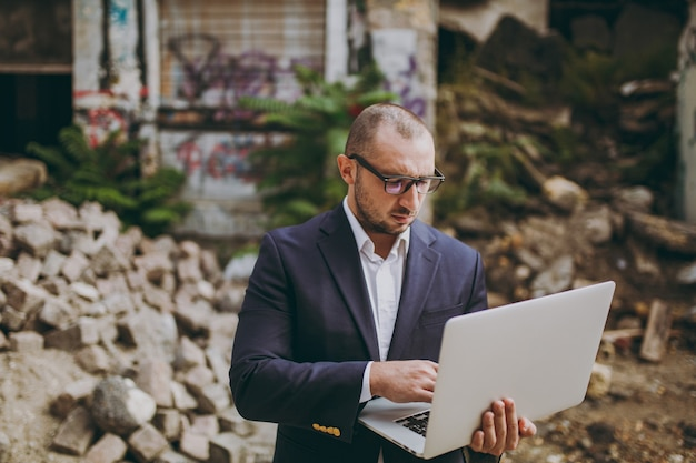 Young successful smart businessman in white shirt, classic suit, glasses. man standing and working on laptop pc computer near ruins, debris, stone building outdoors. mobile office, business concept.