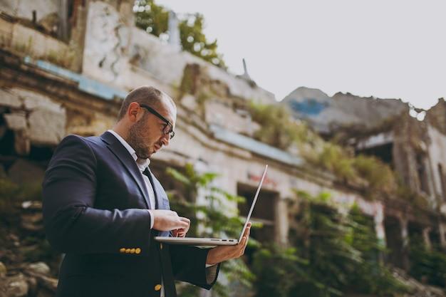 Giovane uomo d'affari intelligente di successo in camicia bianca, abito classico, occhiali. uomo in piedi e al lavoro su un computer portatile vicino a rovine, detriti, edifici in pietra all'aperto. ufficio mobile, concetto di affari.
