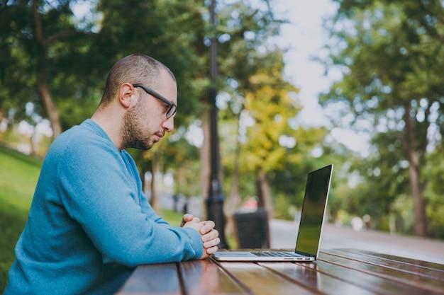 カジュアルな青いシャツ、ラップトップを使用して都市公園で携帯電話でテーブルに座って、屋外で作業している若い成功した賢い人のビジネスマンまたは学生。モバイルオフィスのコンセプト。側面図。