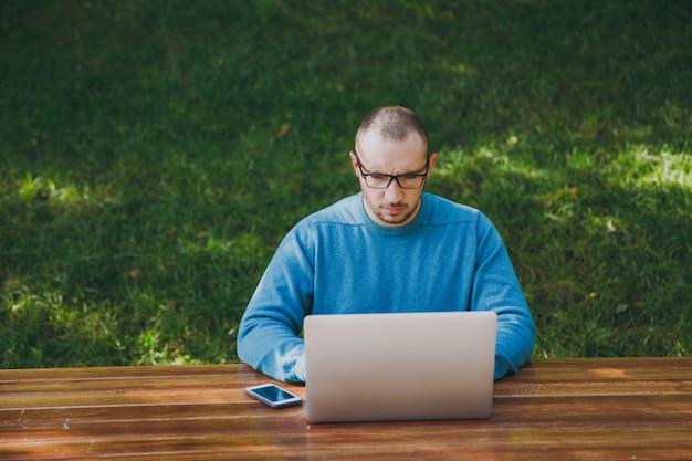 緑の背景で屋外で作業ラップトップを使用して都市公園で携帯電話とテーブルに座っているカジュアルな青いシャツのメガネで若い成功したスマートな男のビジネスマンまたは学生。モバイルオフィスのコンセプト。
