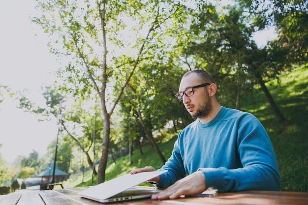 緑の自然で屋外で作業ラップトップを使用して都市公園で携帯電話とテーブルに座ってカジュアルな青いシャツのメガネで若い成功したスマートな男のビジネスマンまたは学生。モバイルオフィスのコンセプト。