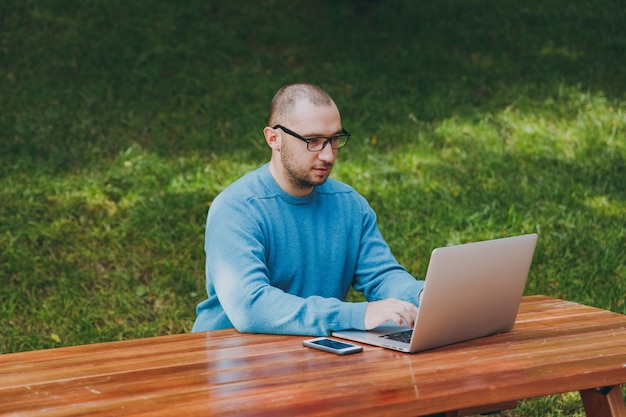 Young successful smart man businessman or student in casual blue shirt glasses sitting at table with mobile phone in city park using laptop working outdoors on green background. mobile office concept.