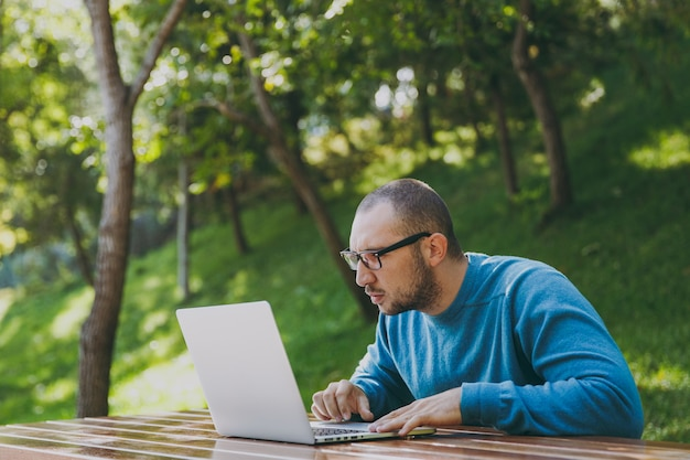Young successful smart man businessman or student in casual blue shirt glasses sitting at table with mobile phone in city park using laptop working outdoors on green nature. mobile office concept.