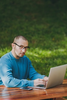 Young successful smart man businessman or student in casual blue shirt, glasses sitting at table with mobile phone in city park using laptop, working outdoors, looking camera. mobile office concept.