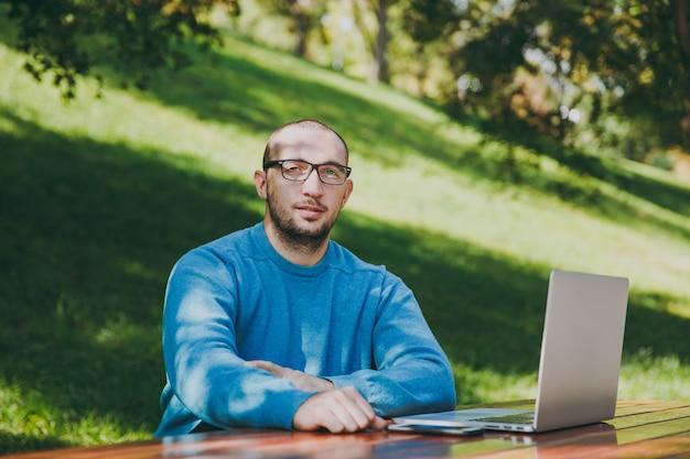 若い成功したスマートな笑顔の幸せな男のビジネスマンやカジュアルな青いシャツの学生、ラップトップを使用して、屋外で作業している都市公園で携帯電話でテーブルに座っている眼鏡。モバイルオフィスのコンセプト。