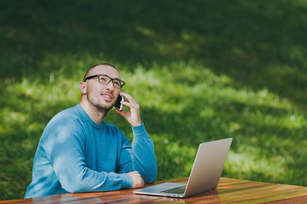 カジュアルな青いシャツ、テーブルに座って、ラップトップを使用して都市公園で携帯電話で話している、屋外で作業している若い成功した笑顔のスマートな男のビジネスマンや学生。モバイルオフィスのコンセプト。
