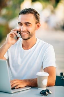 Молодой успешный улыбающийся умный человек или студент в повседневной рубашке, очках, сидя за столом, разговаривает по мобильному телефону в городском парке, используя ноутбук, работая на открытом воздухе. концепция мобильного офиса