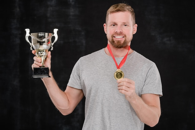Young successful sportsman showing you silver cup and gold medal while standing in front of camera against black background