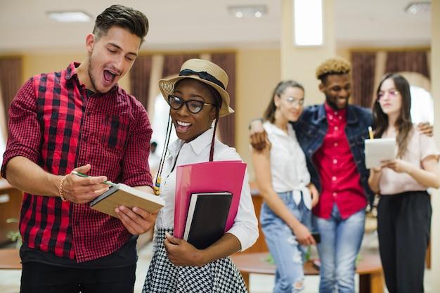 Молодые успешные студенты позируют с ноутбуком