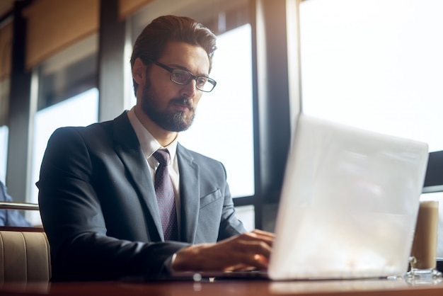 Young successful stylish focused handsome bearded businessman in the suit looking at a laptop on the desk in a cafe or restaurant.