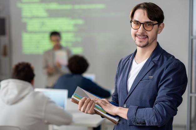 Молодой успешный учитель в повседневной одежде и очках смотрит на вас с улыбкой