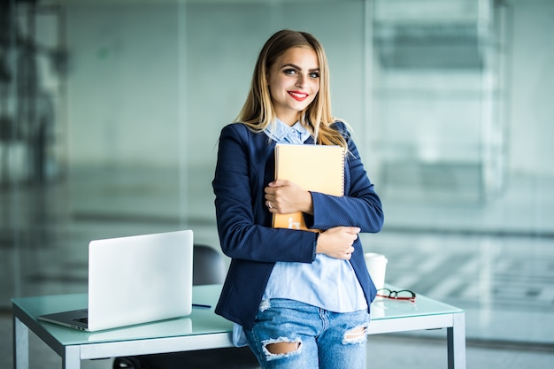 Giovane donna di successo in abiti casual che tengono notebook lavoro in piedi vicino alla scrivania bianca con il computer portatile in ufficio. realizzazione del concetto di carriera aziendale.