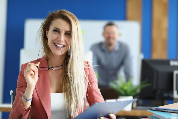 안경을 입 근처에 들고 사무실에서 동료의 배경에 대해 웃고 있는 성공적인 젊은 여성. 비즈니스 교육 개념
