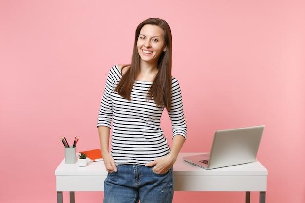 ポケットに手をつないで働く若い成功した女性は、パステルピンクの背景に分離されたpcラップトップで白い机の近くに立っています。業績ビジネスキャリアコンセプト。広告用のスペースをコピーします。