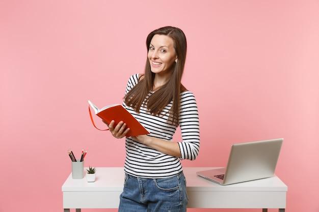 パステルピンクの背景に分離された現代的なpcラップトップと白い机の近くに立っているノートブックの仕事を保持しているカジュアルな服を着た若い成功した女性。業績ビジネスキャリアコンセプト。スペースをコピーします。