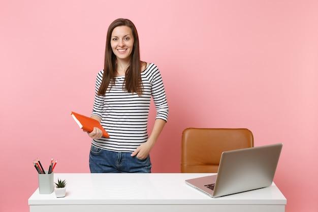現代的なpcのラップトップで白い机の近くに立っているノートブックの仕事を保持しているカジュアルな服を着た若い成功した女性