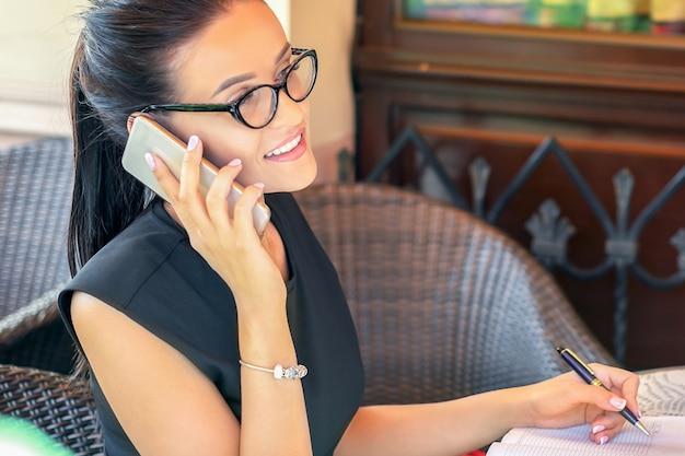 Young successful woman is talking by the phone sitting in a cafe.