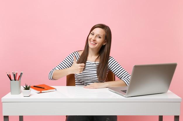 Молодая успешная женщина показывает палец вверх сидит и работает за белым столом с современным портативным компьютером