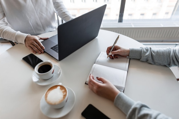現代のオフィスで男性マネージャーと一緒に働くテーブルに座っている若い成功した女性