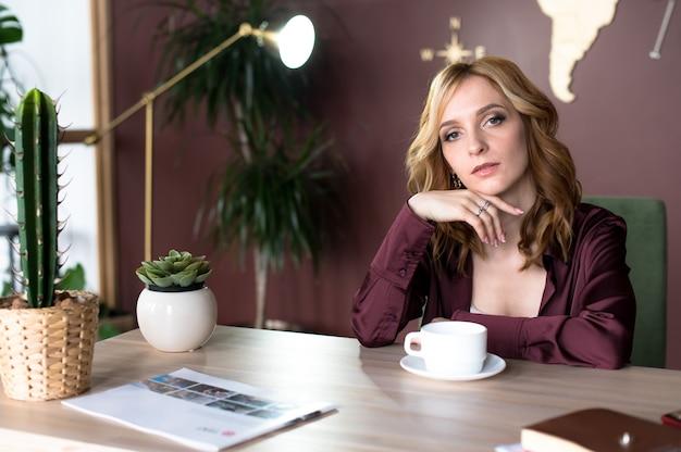 現代のキャビネットに座っている若い成功した女性。コピースペース
