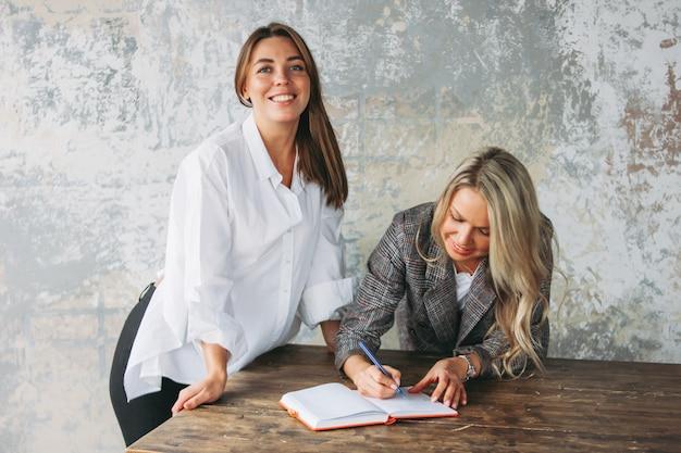 성공적인 젊은 여성 동료는 테이블, 코칭 또는 멘토링에서 공동 프로젝트를 논의