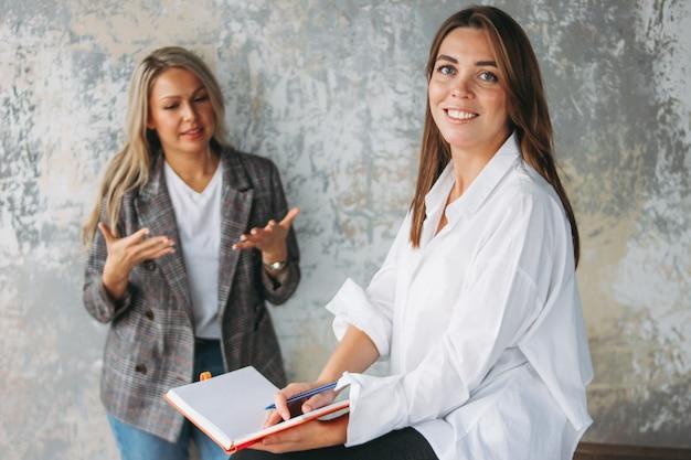 成功した若い女性の同僚が、共同プロジェクト、コーチング、または近代的なロフトオフィスでのメンタリングについて話し合う