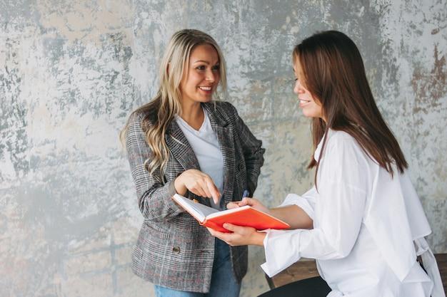 성공적인 젊은 여성 동료 현대 로프트 사무실에서 공동 프로젝트, 코칭 또는 멘토링 논의