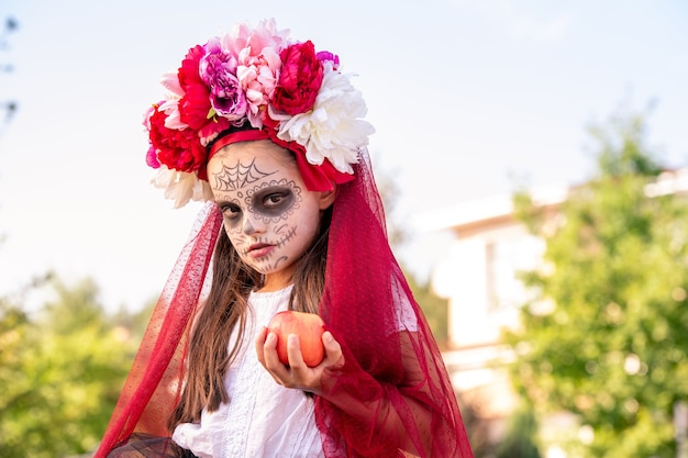 Молодая угрюмая девушка с хэллоуинской краской на лице и красивыми цветами на голове держит красное спелое яблоко перед камерой