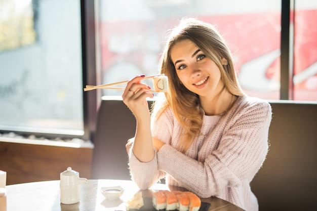 Giovane donna bionda sorridente piena di sole in maglione bianco che mangia sushi per pranzo in un piccolo caffe
