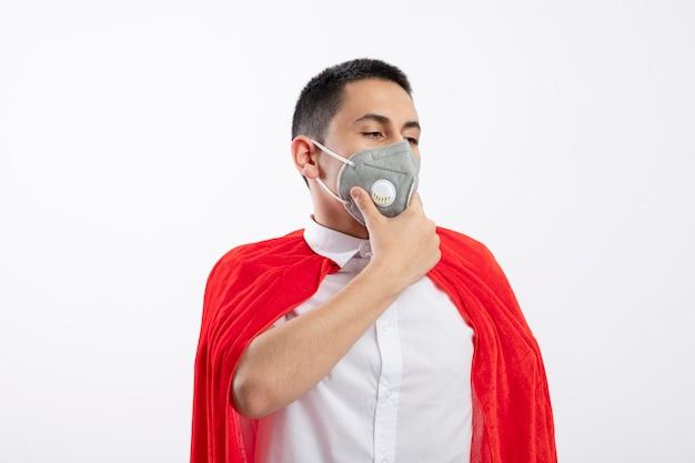 복사 공간 흰색 배경에 고립 내려다보고 턱에 손을 유지 보호 마스크를 쓰고 빨간 케이프에서 젊은 슈퍼 히어로 소년