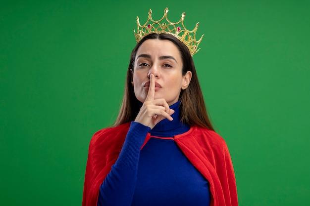 緑に分離された沈黙のジェスチャーを示す王冠を身に着けている若いスーパーヒーローの女の子