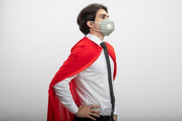넥타이와 엉덩이에 손을 댔을 의료 마스크를 쓰고 프로필보기에 서있는 젊은 슈퍼 히어로 남자