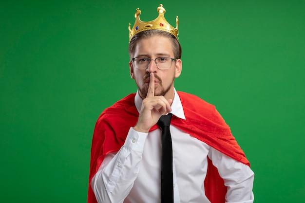 緑に分離された沈黙のジェスチャーを示す王冠とネクタイを身に着けている若いスーパーヒーローの男
