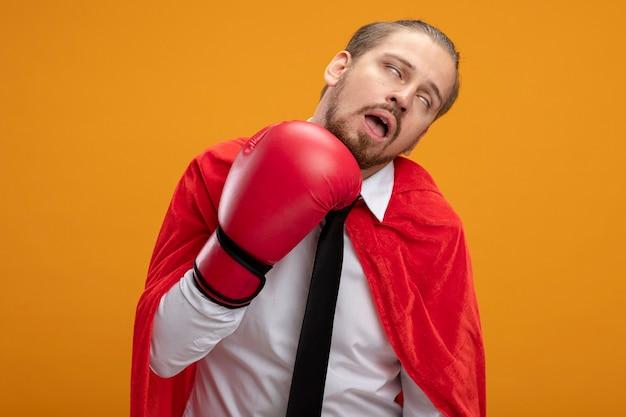 Ragazzo giovane supereroe che indossa cravatta e guantoni da boxe che si batte isolato su arancione