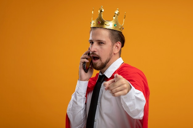 Young superhero guy wearing tie and crown looking at camera speaks on phone showing you gesture isolated on orange background