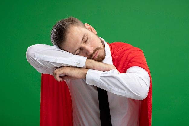 Young superhero guy wearing tie with closed eyes putting head on arms and showing sleep gesture isolated on green