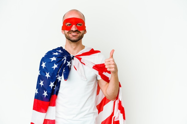 Young superhero man isolated on white wall smiling and raising thumb up